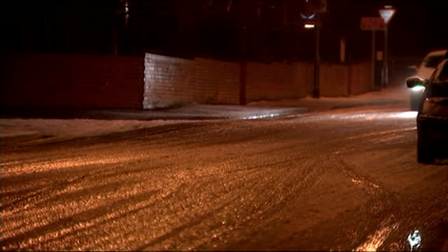 vidéos et rushes de heavy snow fall across large parts of uk affects transport; england: ext / night snow falling around streetlights car along wet snow on road snow... - phare de véhicule
