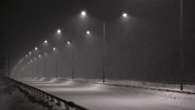stockvideo's en b-roll-footage met heavy snow fall at night - houten paal