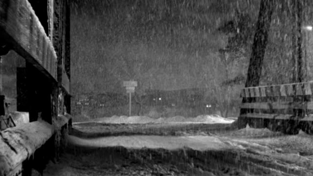 vídeos de stock e filmes b-roll de heavy snow falls as a 1940s police car turns onto a wooden bridge. - 1946