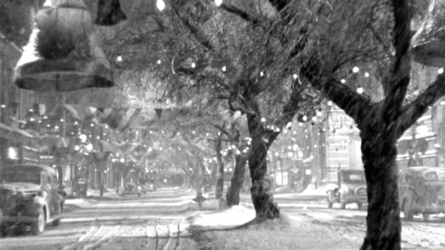 stockvideo's en b-roll-footage met heavy snow falls on a small town's main street decorated for christmas. - 1946