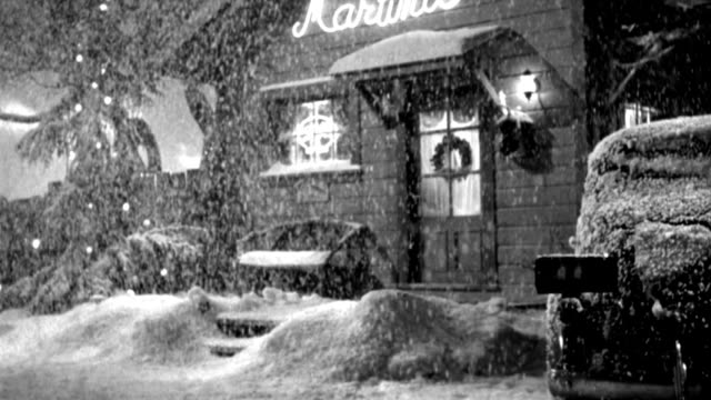 vídeos de stock e filmes b-roll de heavy snow falls outside a cafe decorated for christmas. - 1946