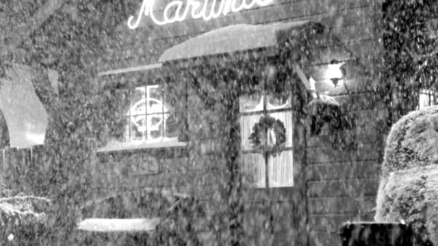 heavy snow falls outside a cafe decorated for christmas. - wreath stock videos & royalty-free footage