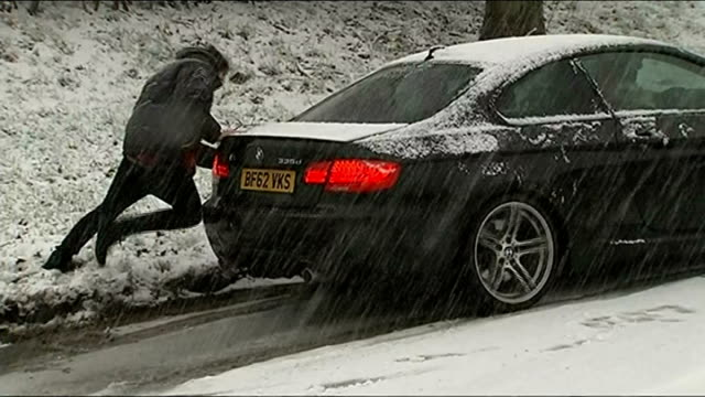 heavy snow in northern england ireland and scotland england cheshire wilmslow ext cars on snow covered road seen from above motorist beside vehicle... - snow vehicle stock videos and b-roll footage