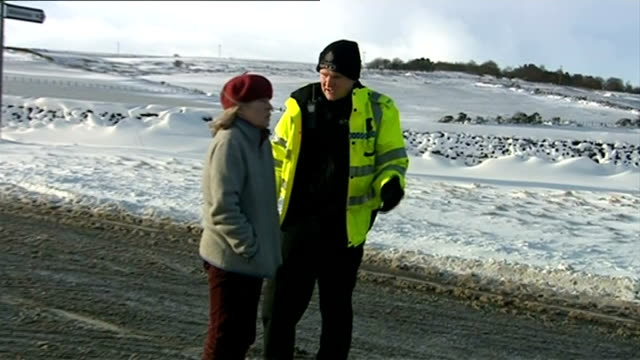 heavy snow in northern england ireland and scotland north east england police officer directing woman motorist on snowy country road police car on... - vox populi stock videos & royalty-free footage