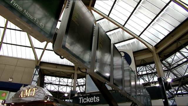 resilience planning SouthEast England INT Passengers about on station concourse TILT UP to information monitors Few passengers along through ticket...