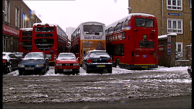 heavy snow nationwide causes further disruption to schools and transport england london buses parked in depot slush covered road in foreground people... - slush stock videos and b-roll footage