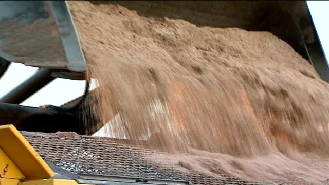 heavy snowfall expected: train companies warn of delays; england: staffordshire: lichfield: ext tractor as tips load of rock salt into back of... - スタッフォードシャー リッチフィールド点の映像素材/bロール