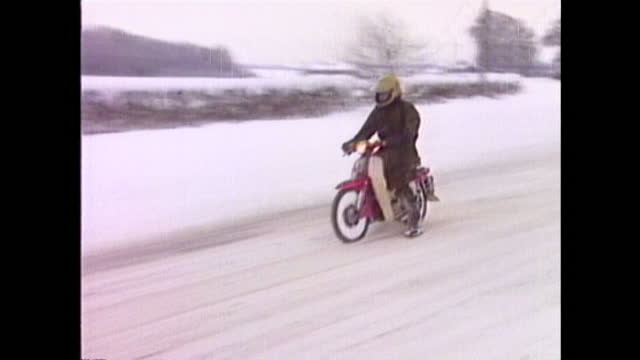 heavy snowfall in eastern england including a telephone box covered with snow and a motorcyclist navigating an icy road in blizzards in january 1987. - frozen stock videos & royalty-free footage