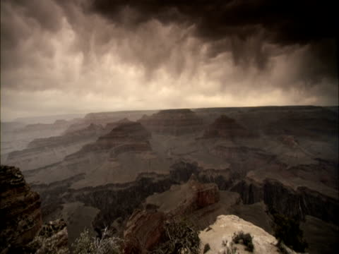 heavy storm clouds loom above the grand canyon. - grand canyon stock videos and b-roll footage