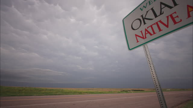 "heavy storm clouds race over a sign reading ""welcome to oklahoma"". - oklahoma stock-videos und b-roll-filmmaterial"