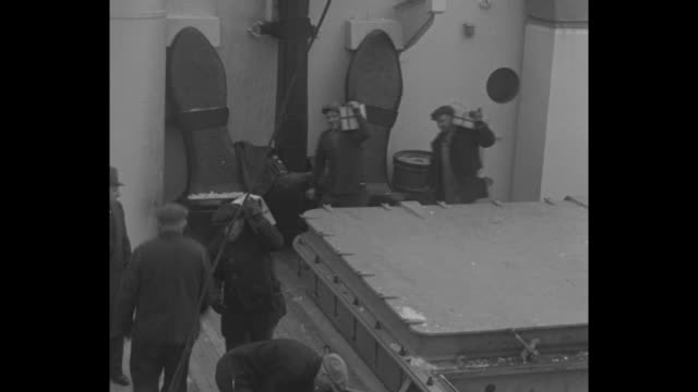 heavy strongbox is hoisted by crane / several men carry gold bars to crates that are then transferred to dock - ingot stock videos & royalty-free footage