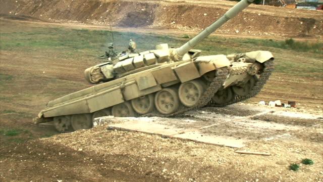 le char lourd surmonte la barrière élevée