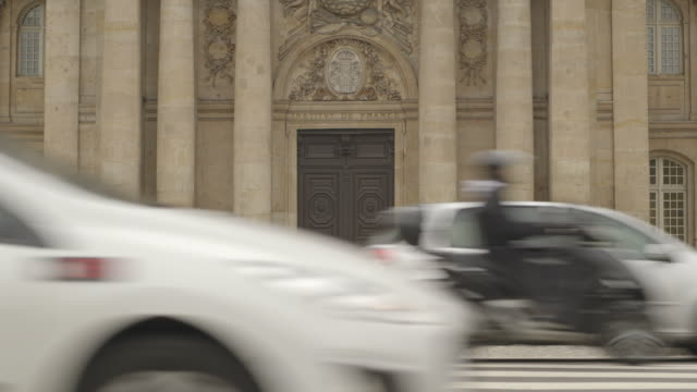 heavy traffic driving along the quai de conti passes the institut de france, paris, france. - moving past video stock e b–roll