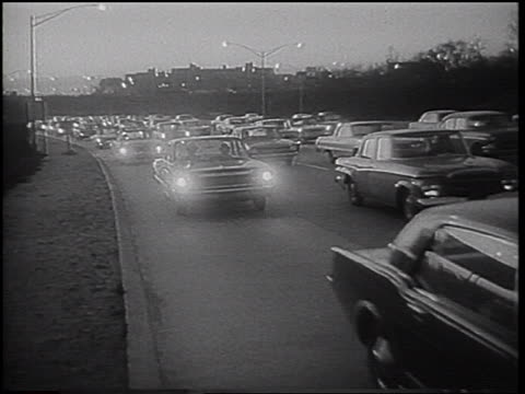 b/w 1966 heavy traffic driving toward past camera on highway in early morning / nyc - 1966 stock-videos und b-roll-filmmaterial