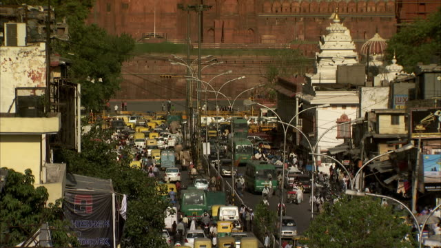 heavy traffic fills a street below delhi's red fort. - bbc stock videos and b-roll footage