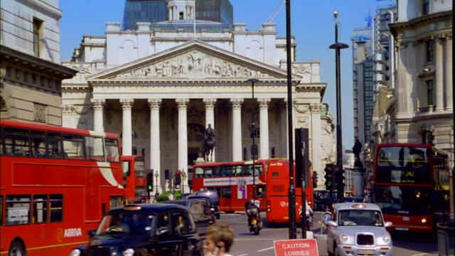 vídeos de stock e filmes b-roll de heavy traffic flows past a columned-building in london. - ano 2000
