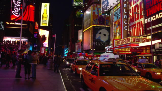 heavy traffic moves along broadway in times square. - broadway manhattan stock-videos und b-roll-filmmaterial