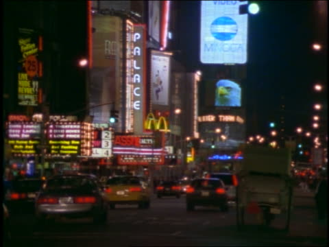 vídeos de stock e filmes b-roll de heavy traffic + neon signs at times square at night / new york city - 1997