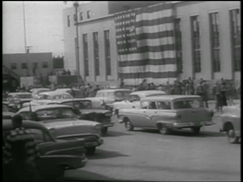 heavy traffic on anchorage street with giant american flag on bldg in background / alaska statehood - 1958 stock videos & royalty-free footage