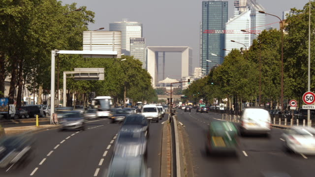 stockvideo's en b-roll-footage met t/l heavy traffic on avenue charles de gaulle going through la defense business district / paris, ile de france, france - breedbeeldformaat