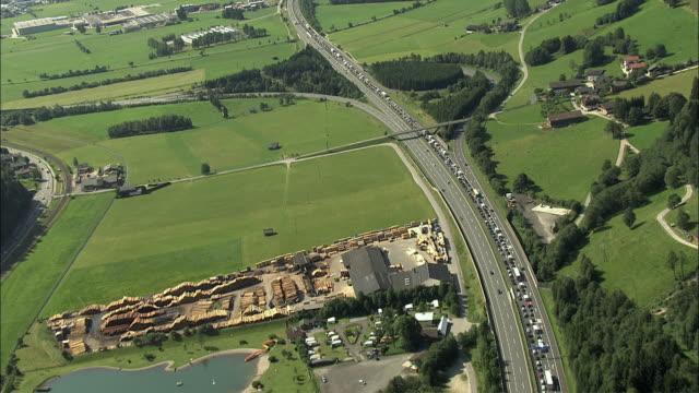 aerial heavy traffic on highway a8 crossing rural landscape near flachau / salzburg, austria - österreich stock-videos und b-roll-filmmaterial
