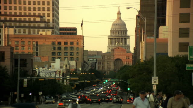 ws, heavy traffic on street, texas state capitol in background, austin, texas, usa - austin texas video stock e b–roll