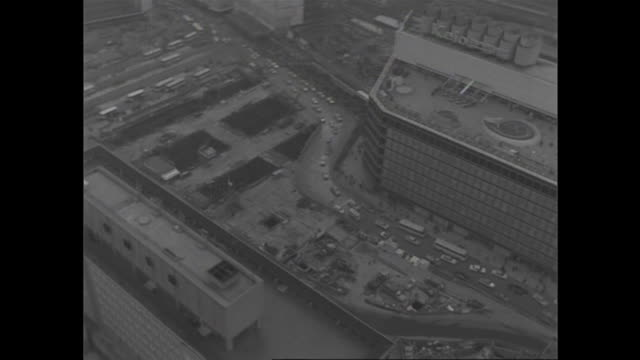 heavy traffic passes shinjuku station's west gate in postwar tokyo. - black and white点の映像素材/bロール