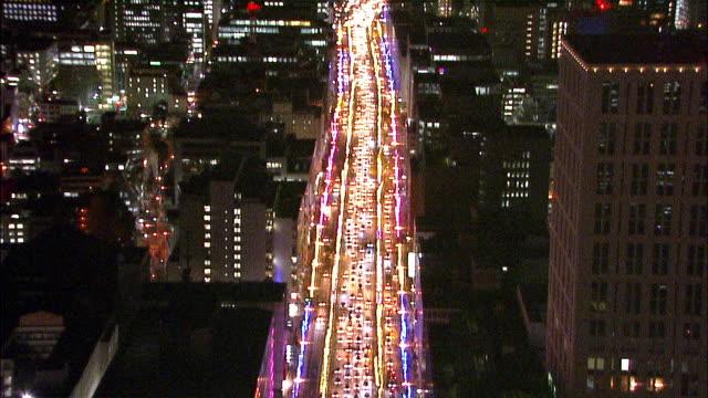 heavy traffic streams along the illuminated midosuji boulevard in osaka. aerial shot - osaka stock videos and b-roll footage