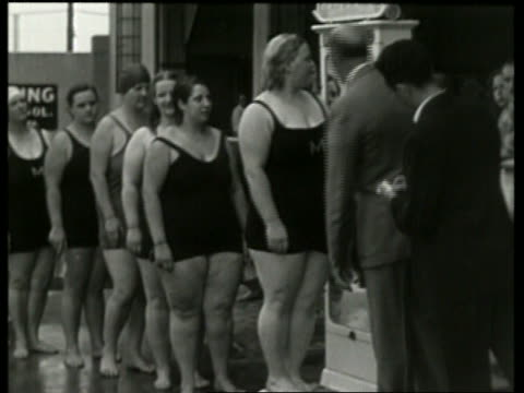 B/W heavy women in swimsuits weighing-in on scale / NO SOUND