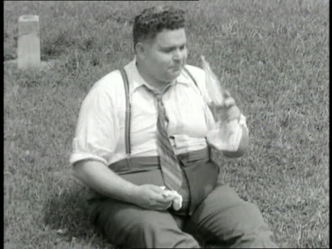 heavyset man wearing suspenders takes a drink from a bottle of soda and wipes his brow. - suspenders stock videos & royalty-free footage