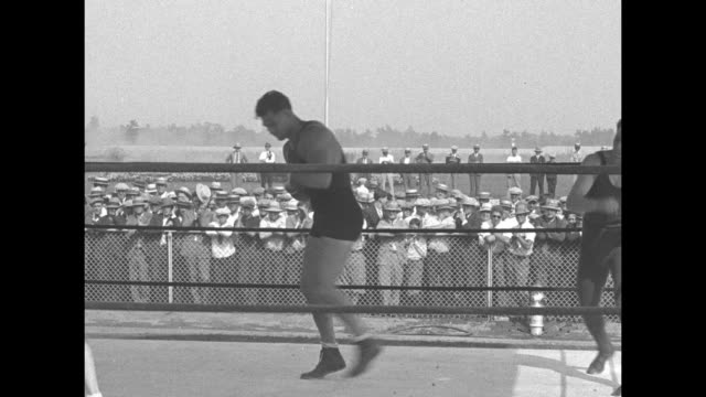 Heavyweight boxer Jack Dempsey shadow boxes in boxing ring as trainer watches at Lincoln Park training site spectators sit along front of building...