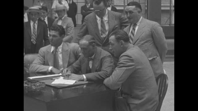 heavyweight boxers jack dempsey and jack sharkey and promoter tex rickard sign bout contract at desk as journalists look on / dempsey and sharkey... - journalist stock videos & royalty-free footage
