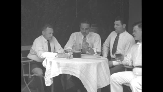 Heavyweight boxers Jack Dempsey second from right and Max Baer sitting next to him at table in restaurant in NY City table has a pitcher of beer on...