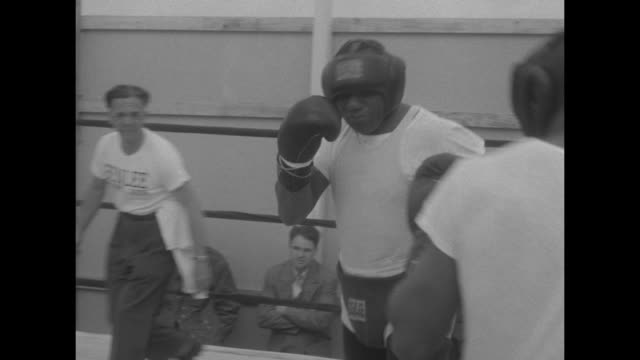 heavyweight champion boxer arnold cream runs along atlantic city boardwalk with trainers with view of us flag on building in background / walcott... - heavyweight stock videos and b-roll footage