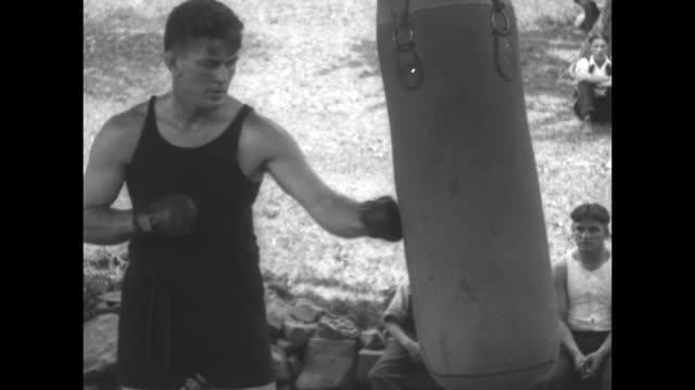heavyweight champion boxer jack dempsey punches heavy punching bag in front of outdoor boxing ring / slow motion shot of dempsey punching heavy bag... - 1926 stock videos & royalty-free footage