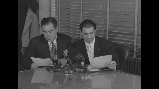 heavyweight champion boxer rocky marciano sits and reads contract with james norris, president of the international boxing club of new york / don... - pesi massimi video stock e b–roll