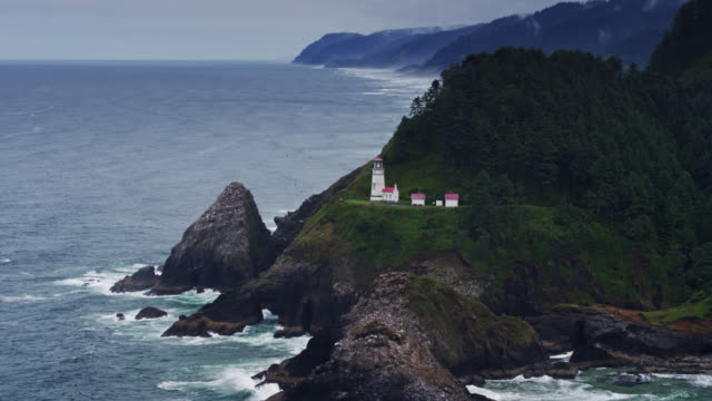 heceta head lighthouse with view up oregon coast - drone shot - heceta head stock videos & royalty-free footage