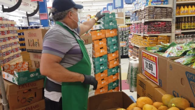 vídeos de stock e filmes b-roll de hector orv restocks the produces shelves as he wears a mask and gloves while working at the presidente supermarket on april 13, 2020 in miami,... - serviços essenciais