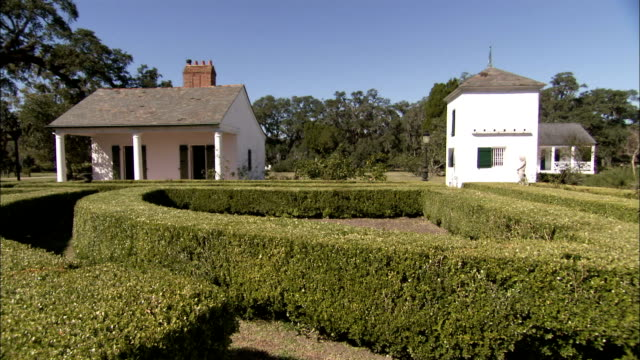 Hedges curve next to outbuildings on the grounds of a plantation. Available in HD.