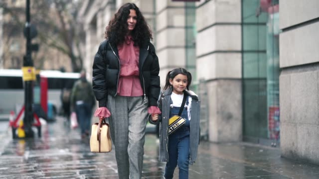hedvig opshaug wears a black puffer jacket, a pink shirt, gray pants, a bag, black shoes ; her daughter wears a gray coat, a shoulder strapped taxi... - celebritet bildbanksvideor och videomaterial från bakom kulisserna