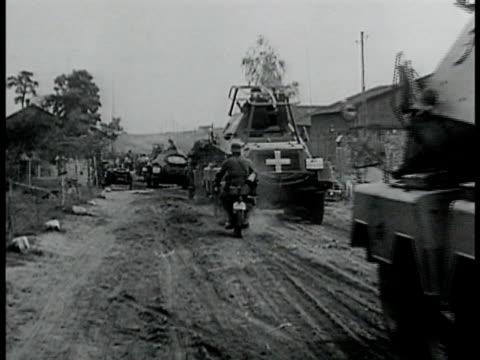 vídeos de stock e filmes b-roll de heinkel he 111 bomber airplane in-flight. german motorists & tank convoy passing through rural village. men walking through town some w/ bandages... - 1939