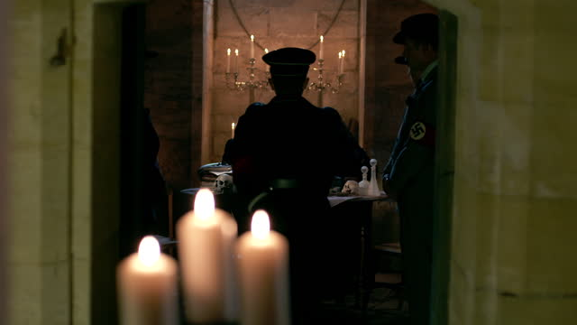 heinrich himmler entering bunker, greeted with a nazi salute from the guard, sits down at the candlelit table with others. - candlelight stock videos & royalty-free footage