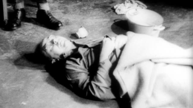 heinrich himmler head of hitler's secret police commits suicide rather than face trial / himmler's dead body on floor syringe next to it / cu hand... - adolf hitler stock-videos und b-roll-filmmaterial
