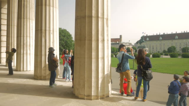 vídeos de stock e filmes b-roll de heldenplatz palace gate pillars with tourists. - mala de ombro