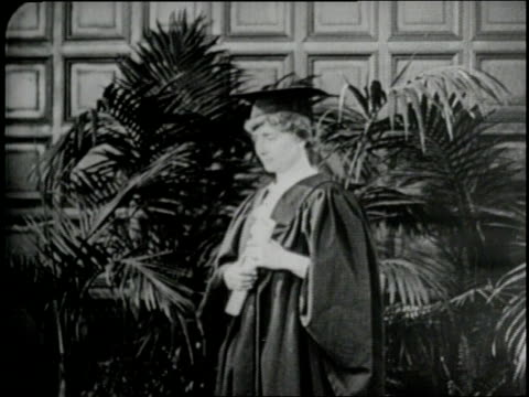 stockvideo's en b-roll-footage met helen keller holds her diploma wearing a cap and gown upon her graduation in 1904 - afstudeer toga