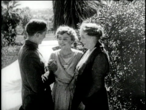 Helen Keller hugs her brother and mother after which he finger spells in her hand as their mother Kate watches