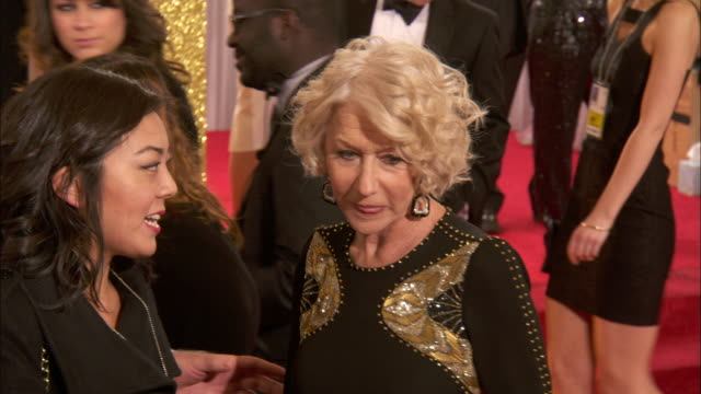 vidéos et rushes de helen mirren w/taylor hackford and handler walking down the red carpet and over to reporters at the beverly hilton hotel - helen mirren