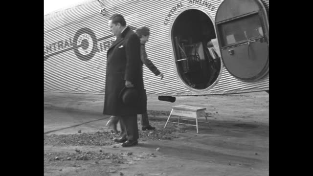 helen richey, america's first female air mail pilot, hands bags of mail to man standing on platform next to airplane / richey shakes hand of the... - 航空便点の映像素材/bロール