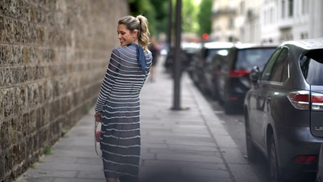 stockvideo's en b-roll-footage met helena bordon wears a blue lace striped dress a pink bag and heels outside the valentino show during paris fashion week haute couture fall/winter... - week