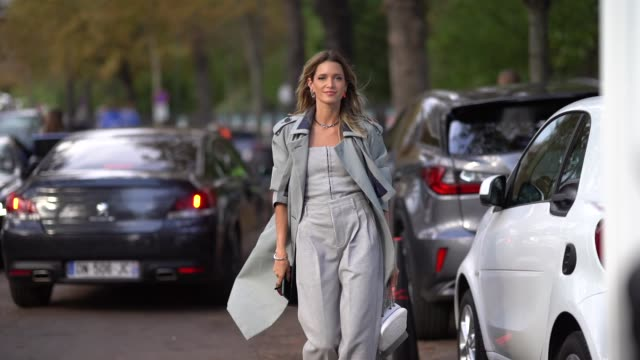 helena bordon wears a gray trench coat, a gray off-shoulder top, flare pants, outside lacoste, during paris fashion week - womenswear spring summer... - トレンチコート点の映像素材/bロール